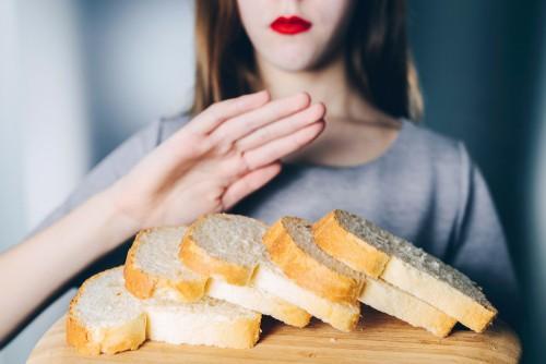 celiac disease woman gesturing refusal of offered bread