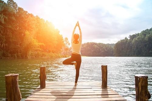 woman doing yoga on dock by lake