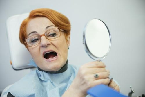 lady examines teeth in mirror in dental chair